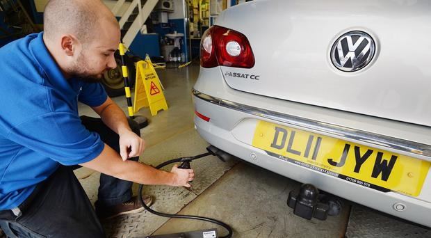 A Volkswagen Passat CC car is tested for exhaust emissions, at a MOT (Ministry of Transport) testing station in Walthamstow, north-east London