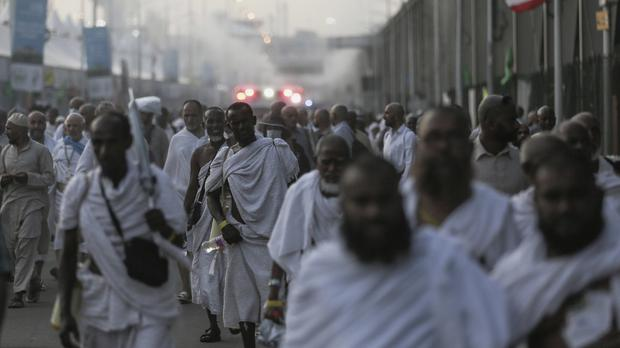 Pilgrims walk by the site where hundreds were killed during the annual hajj in Saudi Arabia (AP)