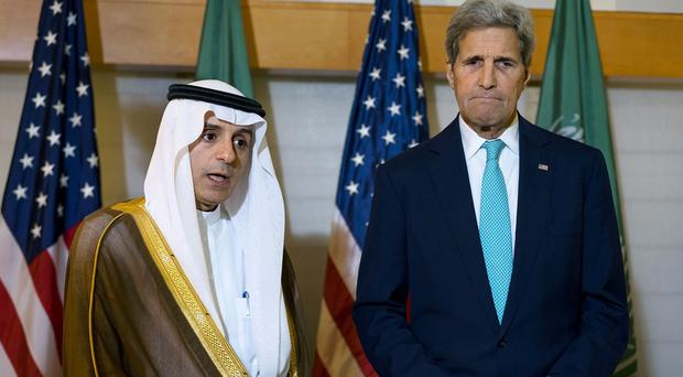 A grim-faced John Kerry looks on as Saudi Arabia's foreign minister Adel al-Jubeir talks about the hajj stampede (AP)