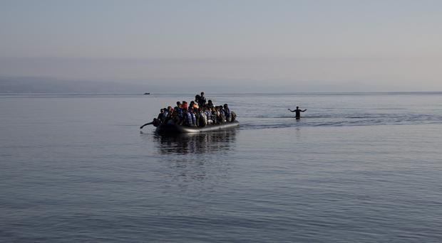 Afghan migrants arrive on the shores of the Greek island of Lesbos after crossing the Aegean sea from Turkey in an inflatable dinghy. (AP)