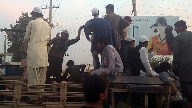 Taliban fighters and young men take over an army truck on a street in Kunduz (AP)