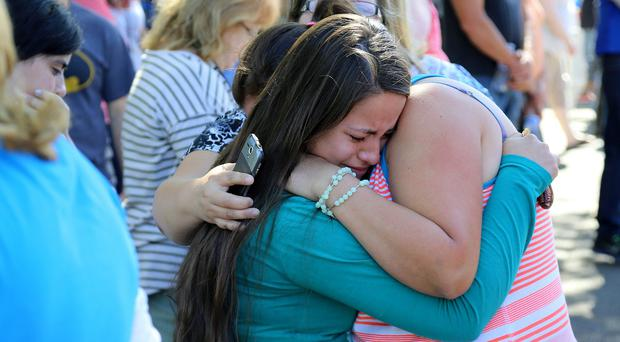 A woman is comforted after a shooting at Umpqua Community College (AP)