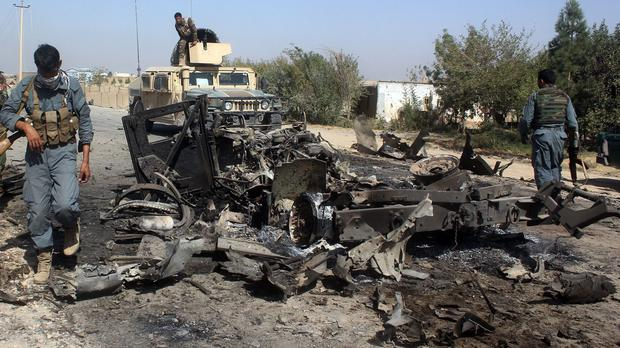 Afghan security forces inspect the site of a US airstrike in Kunduz (AP)