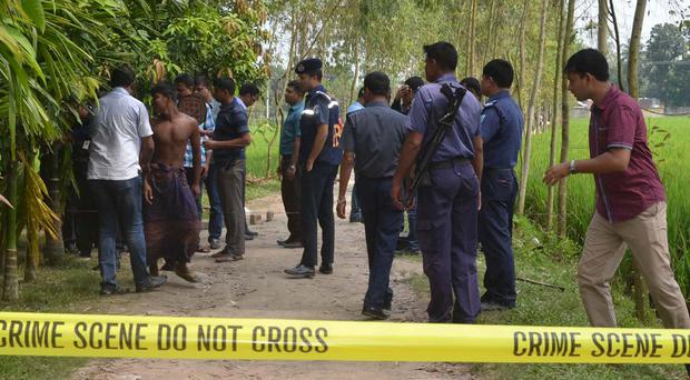 Bangladeshi security officers at the site where Kunio Hoshi was killed (AP)