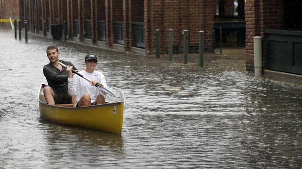 Dillon Christ, front, and Kyle Barnell paddle their canoe down a flooded street in Charleston, South Carolina (AP)