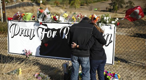 People place flowers at a makeshift memorial near the road leading to Umpqua Community College in Roseburg, Oregon (AP)