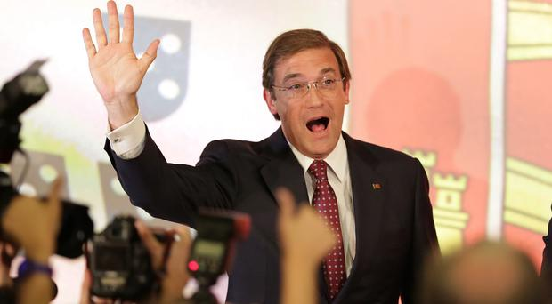 Portuguese prime minister Pedro Passos Coelho waves to supporters following the announcement of the results of the general election in Lisbon (AP)