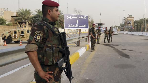 Iraqi security forces stand guard as they check motorists entering the heavily fortified Green Zone in Baghdad (AP)