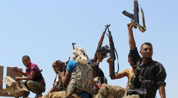 Pro-government forces ride on an armoured vehicle in Yemen. (AP)