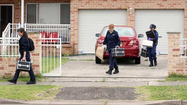 Officers leave a home in the Sydney suburb of Guildford during a series of raids in connection with the murder of a civilian police worker (AP)