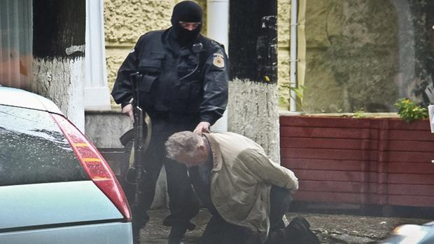 In this June 27, 2011 photo, go-between Teodor Chetrus is detained by a police officer in Chisinau during a uranium-235 sting operation (Moldova Police/AP)