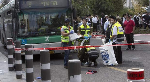 Israeli emergency response members clean the scene of a stabbing attack in Jerusalem (AP)