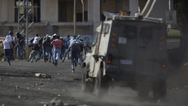 Palestinian protesters run for cover during clashes with Israeli troops near Ramallah. (AP)