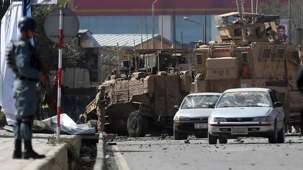 Afghan and foreign soldiers inspect the site of a bomb attack on Nato forces in Kabul (AP)