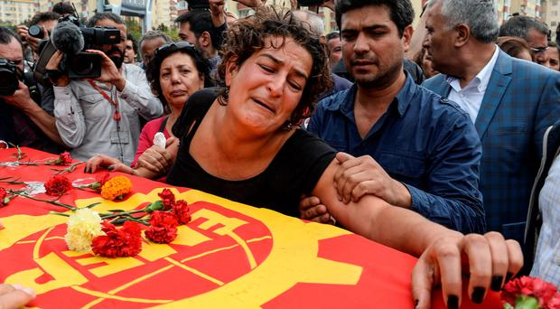 The family of one of the victims of Saturday's blasts mourn over his coffin yesterday