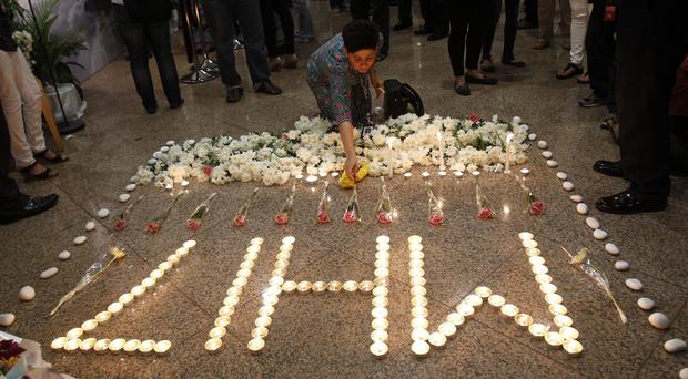 A Malaysia Airlines crew member places a flower next to candles forming the letters MH17 after multi-faith prayers for the victims (AP)