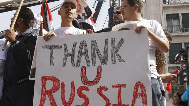 Supporters of the Syrian government hold a pro-Russian banner as they show their support for President Bashar Assad. (AP)