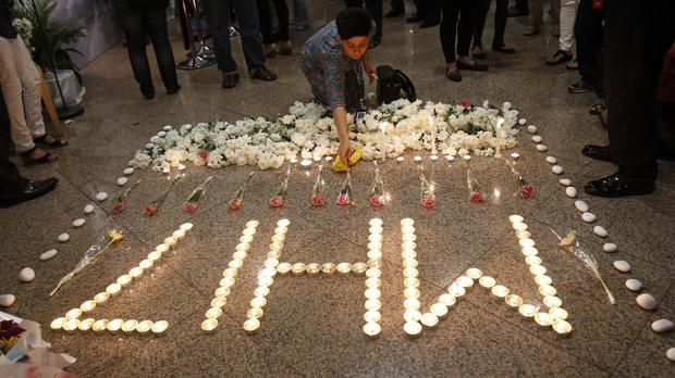 A Malaysia Airlines crew member places a flower next to candles forming the letters MH17. (AP)