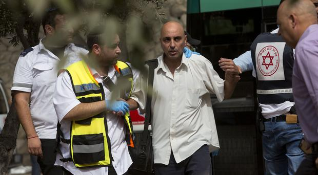 Israeli medics walk with an Israeli man at the scene of a shooting attack in Jerusalem. (AP)