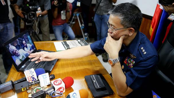 Colonel Restituto Padilla, spokesman of the Armed Forces of the Philippines, watches the video purportedly showing the abductees. (AP)