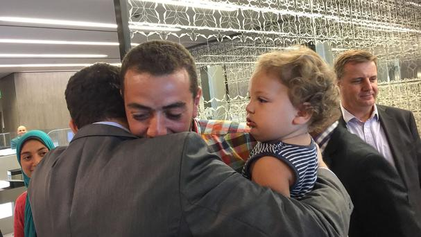 Egyptian Al-Jazeera English journalist Baher Mohammed, carrying his son Haroon, is welcomed by his colleagues upon his arrival in Qatar. (AP)