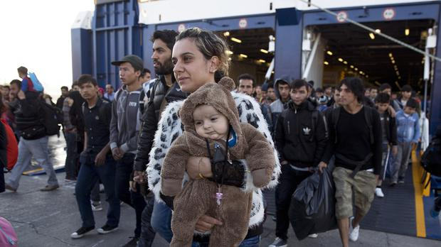 A Syrian woman carrying a baby disembarks from a ferry in Athens upon arrival from the Greek island of Lesbos (AP)