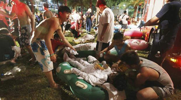Emergency rescue workers and concert goers are seen tending to injured victims from an explosion during a music concert at the Formosa Water Park Taiwan (AP)