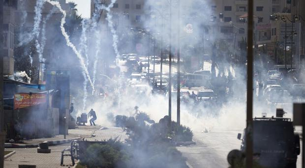 Israeli troops fire tear gas during clashes with Palestinian demonstrators near Ramallah. (AP)