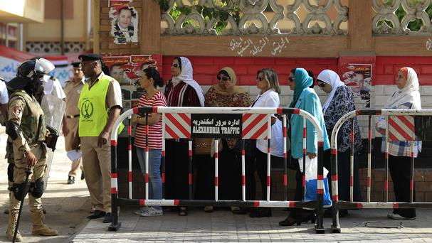 Egyptians wait to cast their votes outside a polling station (AP)