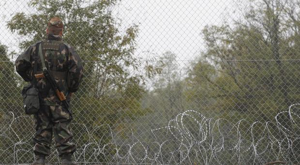 A Hungarian soldier stands by a fence that was set up at the border with Croatia (AP)