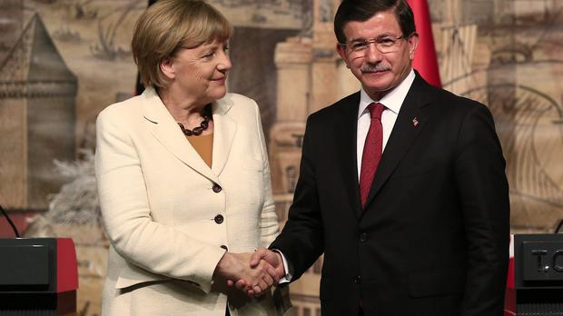 Germany's Chancellor Angela Merkel shakes hands with Turkish prime minister Ahmet Davutoglu at a joint press conference in Istanbul (AP)