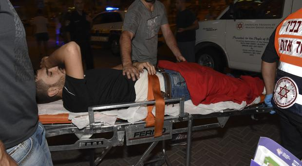 A wounded Israeli policeman is evacuated from the scene of an attack in Beersheba. (AP)