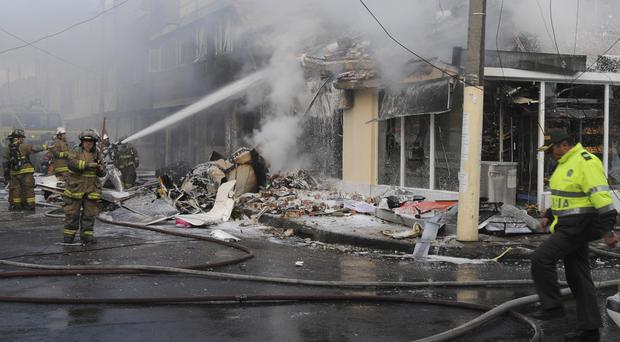 Firefighters spray water on a bakery set on fire after a small plane crashed into it in Bogota. (AP)