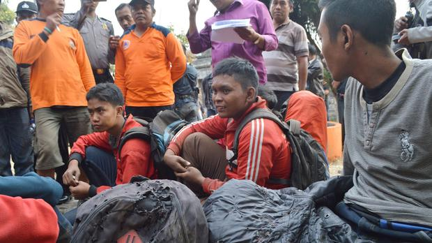 Hikers who escaped the forest fire on Lawu Mountain rest at Cemoro Sewu, East Java. (AP)