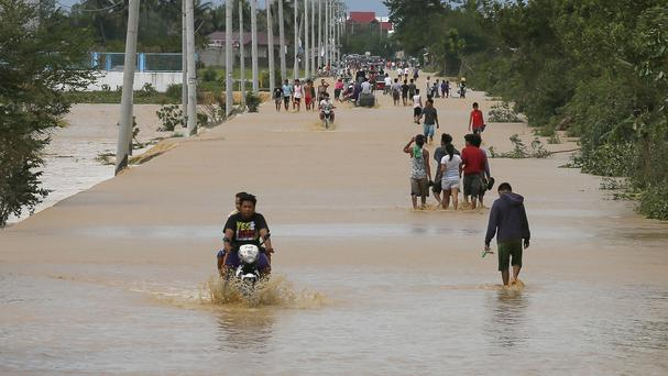 Residents wade through flood waters brought about by Typhoon Koppu at Zaragosa township in Nueva Ecija province north of Manila. (AP)