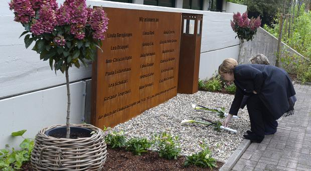 German chancellor Angela Merkel lays down flowers at a memorial at the Joseph-Koenig high school in Haltern, Germany (Roberto Pfeil/Pool Photo via AP)