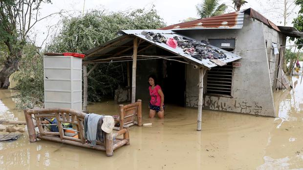 A resident wades through her flooded home in Cabanatuan, northern Philippines after Typhoon Koppu battered the city. (AP)