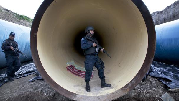 Police guard a drainage pipe outside the Altiplano maximum security prison in Almoloya after El Chapo's escape (AP)