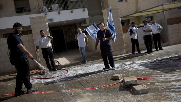 An Israeli man cleans blood stains at the scene of a stabbing attack in Beit Shemesh, central Israel (AP)