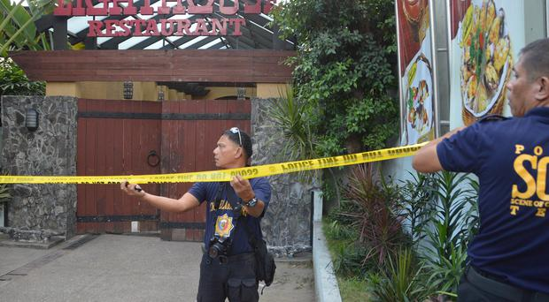Police mark the crime scene with tape where two Chinese diplomats were killed in Cebu province, central Philippines. (AP)