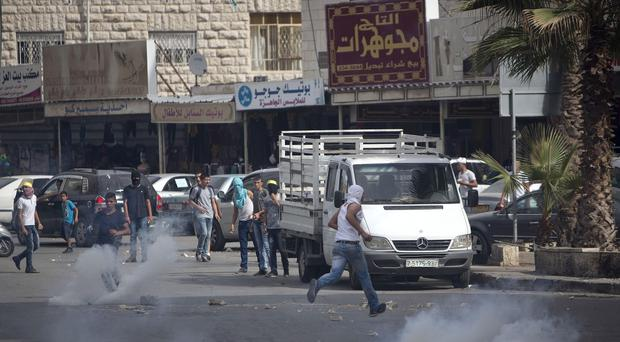 Palestinian protesters run for cover from tear gas fired by Israeli soldiers during clashes in the West Bank town of al-Ram (AP)