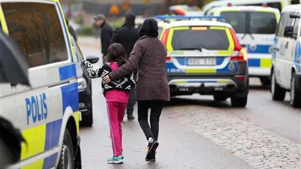 Students and parents leave Kronan school in Trollhattan, Sweden (Bjorn Larsson Rosvall/TT via AP)
