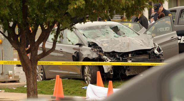Police investigate the wreckage of the car which crashed into spectators during the Oklahoma State University homecoming parade (AP)