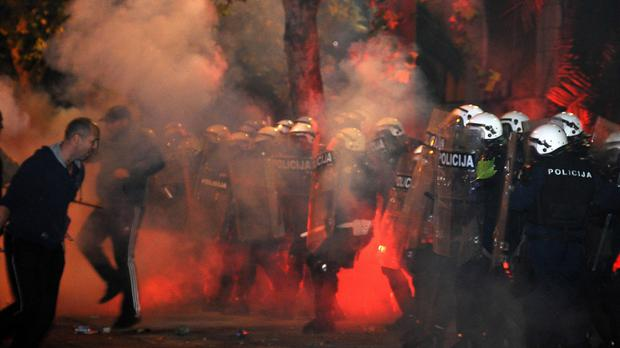 Police are engulfed in smoke and flames as opposition supporters hurl torches during a protest outside the Parliament building in Podgorica (AP)