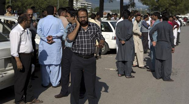 People stand outside their offices after a severe earthquake is felt in Islamabad, Pakistan (AP)