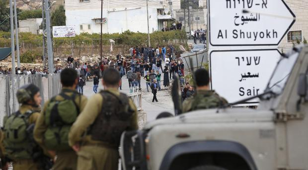 Israeli soldiers and Palestinians stand at the scene of an attack in the West Bank (AP)