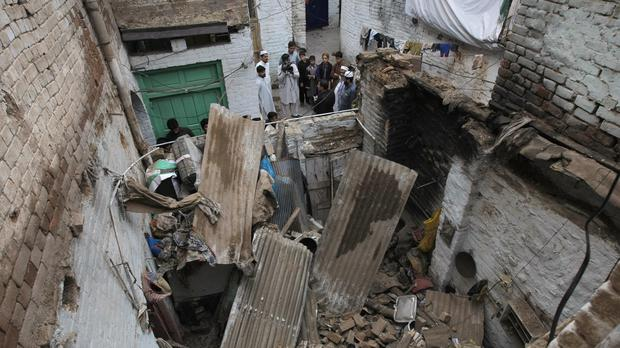 People stand outside a house damaged by the earthquake in Peshawar, Pakistan (AP)