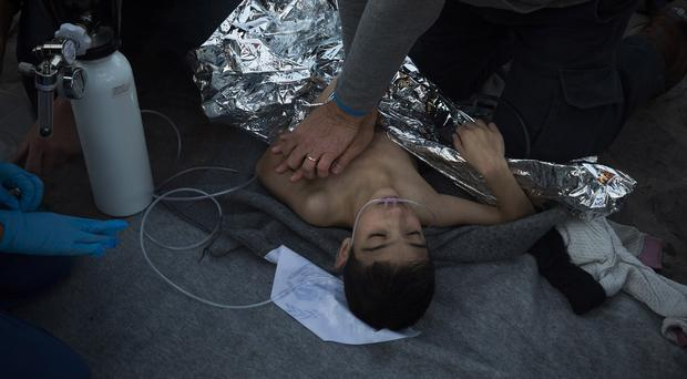 Paramedics and doctors try to revive a young boy after a boat sank near Lesbos (AP)