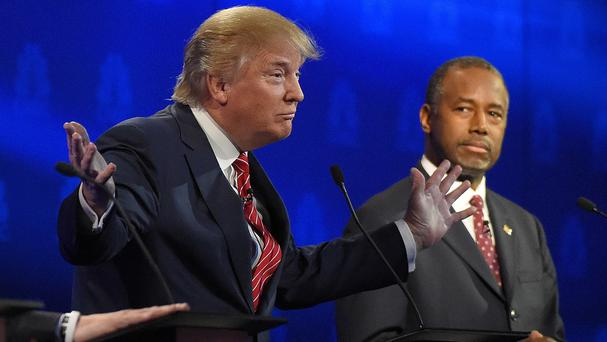 Ben Carson, right, watches as Donald Trump speaks during the Republican presidential debate (AP)
