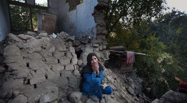 A woman mourns as she sits on the rubble of her destroyed home, in Jinjara village in Chitral, a district of northern Pakistan (AP)